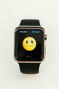 PARIS FRANCE - APR 10 2015: New wearable computer Apple Watch smartwatch displaying the new Smile Emoji. Apple Watch incorporates fitness tracking and health-oriented capabilities and integration with iOS Apple products and services